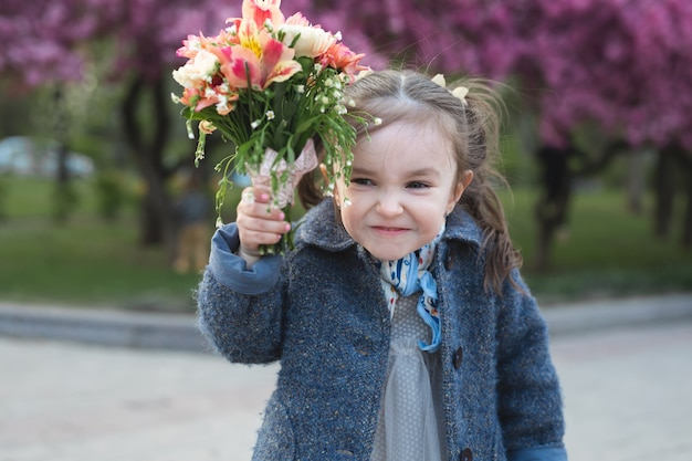 Little girl in a park in the spring is threatening the camera and waving a bouquet of flowers.
