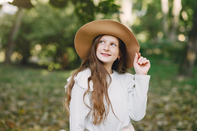 Little girl in a park standing in a park in a brown hat