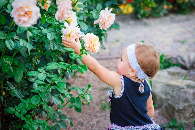 Little girl in the park stretches in roses