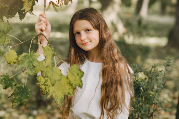 Little girl in a park in a white blouse