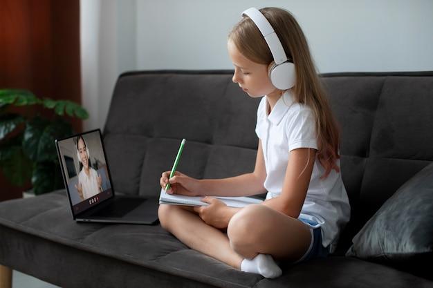 Маленькая девочка участвует в онлайн-классах с наушниками