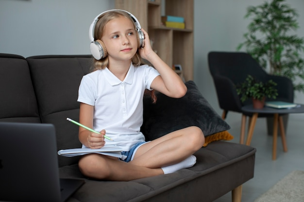 Little girl participating in online classes while using headphones