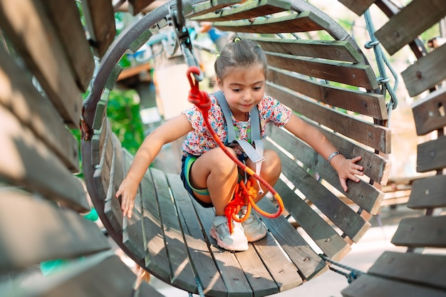 A little girl passes the obstacle in the rope park