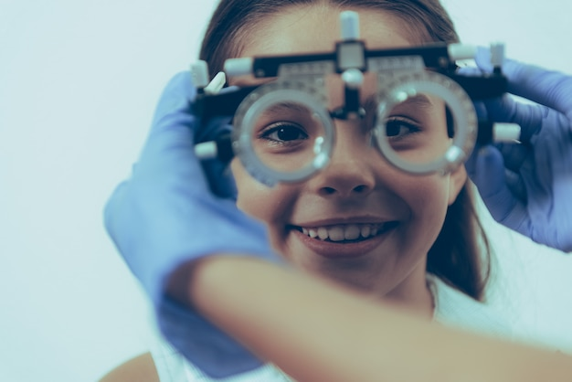 Маленькая девочка пациента на оптический экзамен в клинике