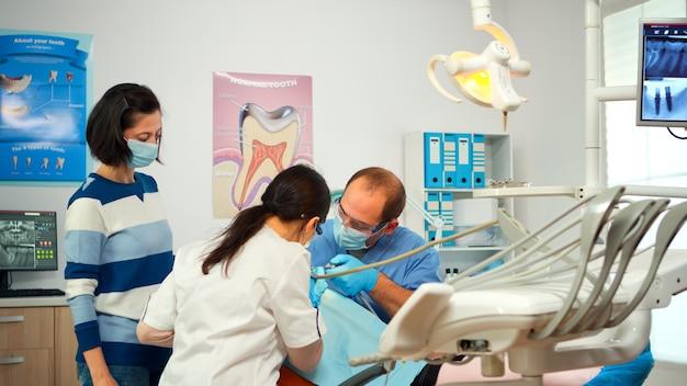 歯科医院の口腔病学の椅子に座って、口腔の問題のために医師を訪ねている少女患者。保護手袋とマスクを持つ女性歯科医は、手術中に虫歯掘削歯を削除します