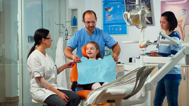 Little girl patient with tooth pain explaining dental problem to pediatric dentist and indicating at toothache with tongue. stomatologist taking with mother about stomatologic examination of kid.