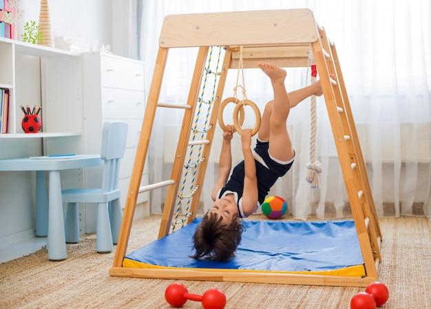 Little girl performs gymnastic exercises on a wooden home sports complex