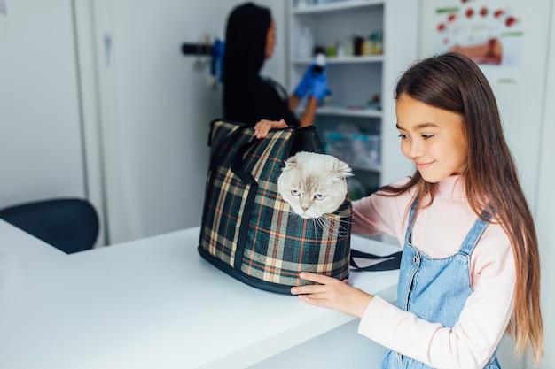 어린 소녀 애완 동물 주인은 산책을 위해 또는 동물 병원에서 특별한 케이지 캐리어에 고양이를 안고 있습니다