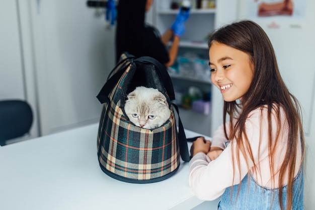 Little girl pet owner carries her cat in a special cage carrier for a walk or in veterinary clinic