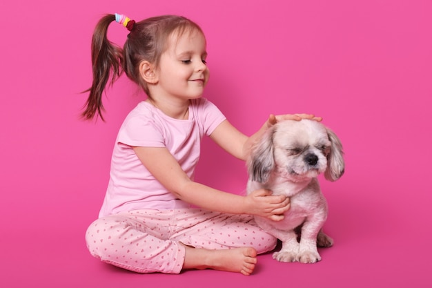 Little girl pets her pekingese while sitting with crossed legs on floor. adorable child likes her pet. cute smiling kid looks at her dog, wears pink shirt and trousers, with pony tails. kids concept.