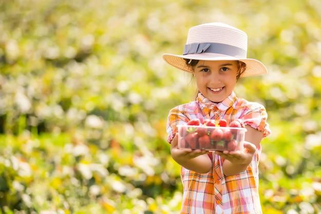 Маленькая девочка собирает клубнику в поле