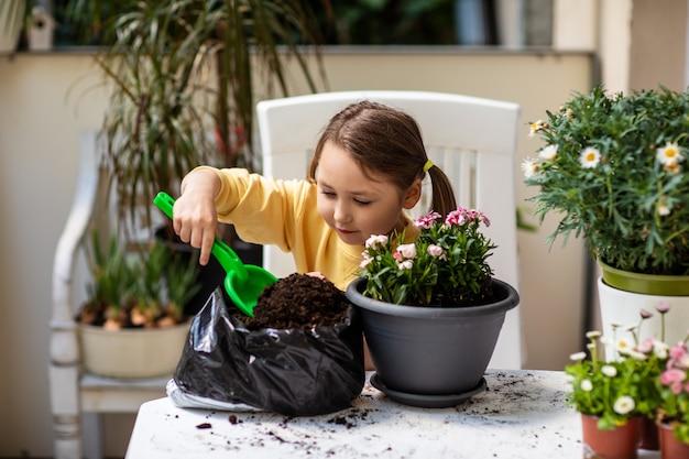 어린 소녀가 삽으로 땅을 집어 들고 발코니에 냄비에 꽃을 심는 데 집중