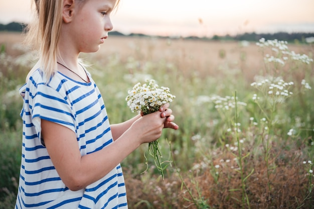 Маленькая девочка собирает полевые цветы в желтом пшеничном поле на закате, летний пейзаж, летний сельскохозяйственный фон со спелыми колосьями пшеницы