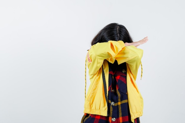 Little girl pillowing face on her arms in checked shirt, jacket and looking sleepy. front view.