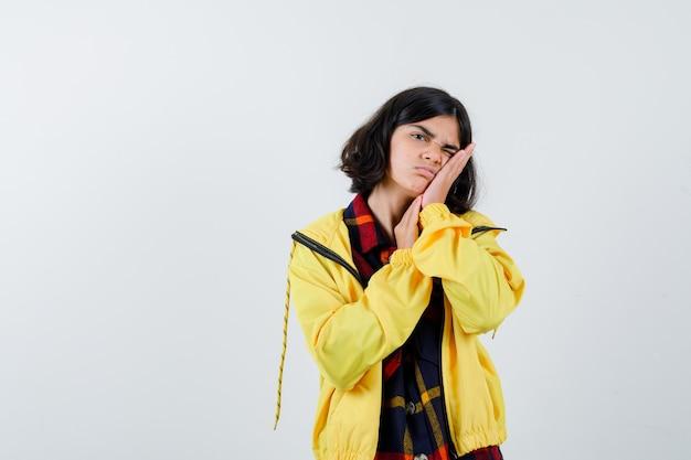 체크 셔츠, 재킷에 그녀의 손에 얼굴을 베개하고 졸린 찾고 어린 소녀