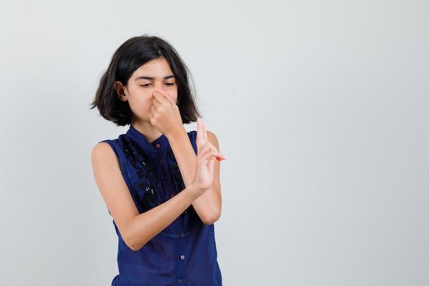 코를 꼬 집 고 파란색 블라우스에 두 손가락을 보여주는 어린 소녀.