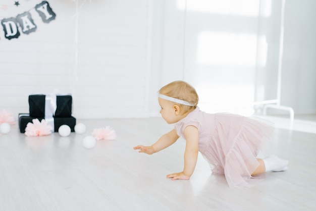 Little girl in a pink dress crawls on the floor