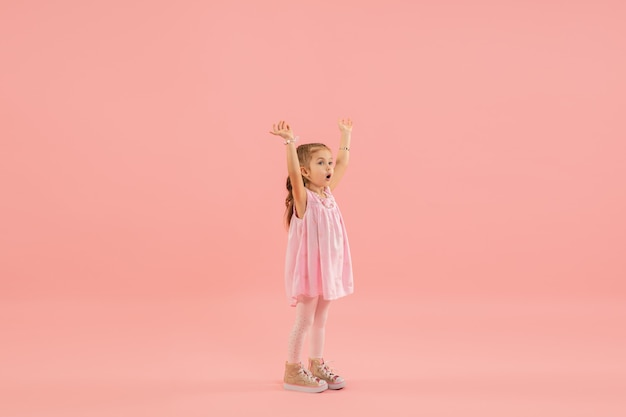 Little girl in pink dress on pink wall