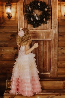 A little girl in a pink dress stands in front of a wooden door with a christmas wreath. welcome to the fairy tale