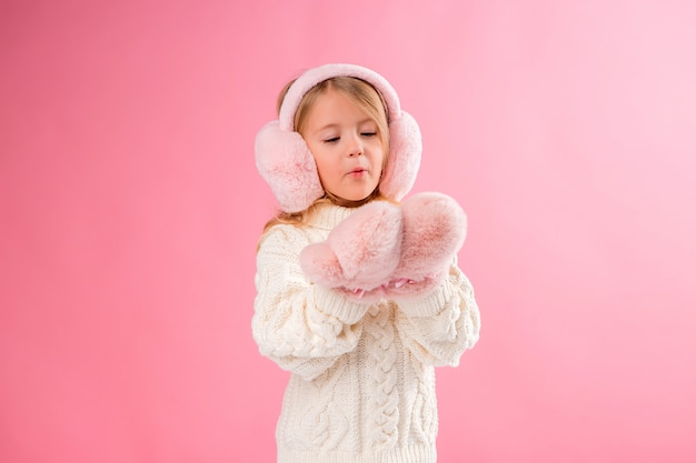 Little girl in pink mittens and headphones on a pink wall