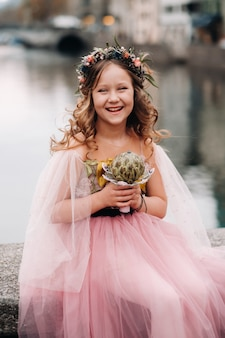 A little girl in a pink princess dress with a bouquet in her hands walks through the old city of zurich.