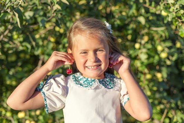 Little girl in pink shirt and denim skirt, holding cherries in her hands like ears
