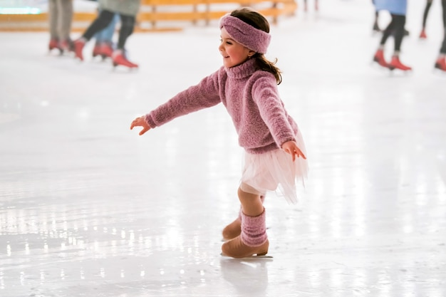 Little girl in a pink sweater is skating on a winter evening on an outdoor ice rink lit by garlands