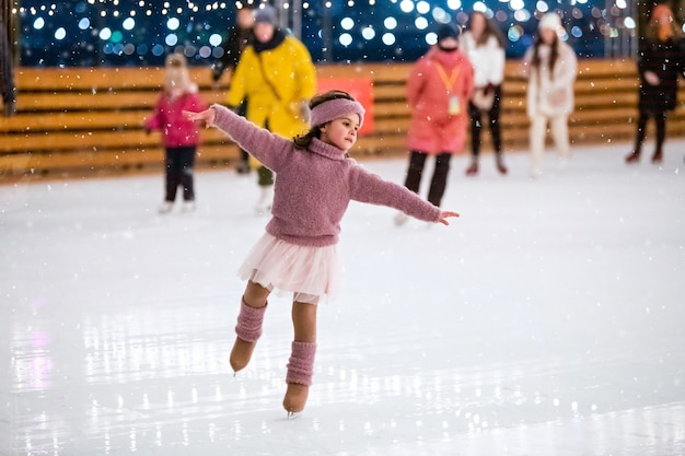 Little girl in pink sweater skates on a winter snowy evening at an outdoor ice rink