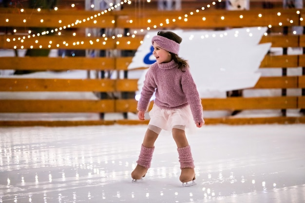 Little girl in a pink sweater and a skirt is skating on a winter evening on an outdoor ice rink lit with garlands