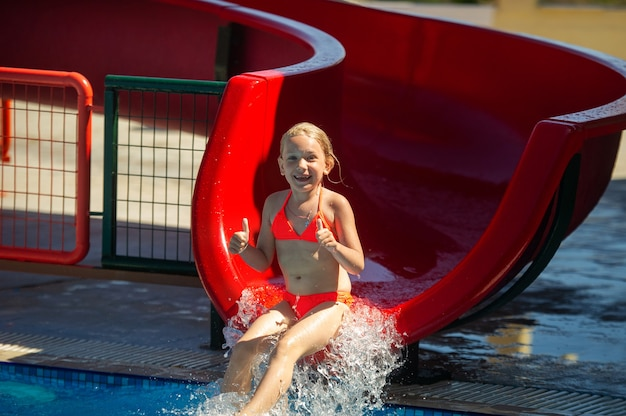 A little girl in a pink swimsuit slides down a water slide in a water park during the summer