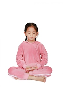Little girl in pink tracksuit with eyes closed practicing mindfulness meditation
