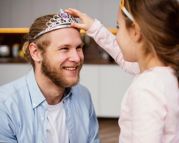 Маленькая девочка надевает диадему на голову отца