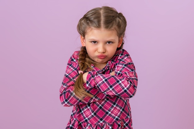 A little girl in a plaid dress and with pigtails on her head holds her hands near her chest and looks very offended.