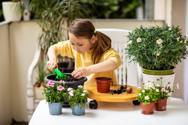 Little girl planting flowers on the balcony, caring for plants