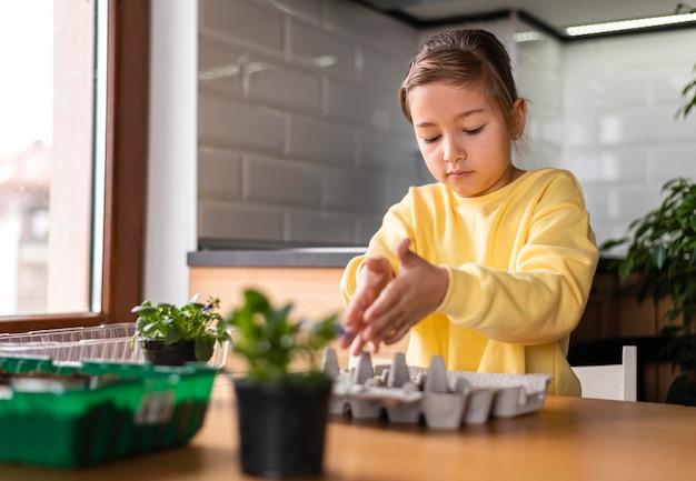 집에서 씨앗을 심는 어린 소녀
