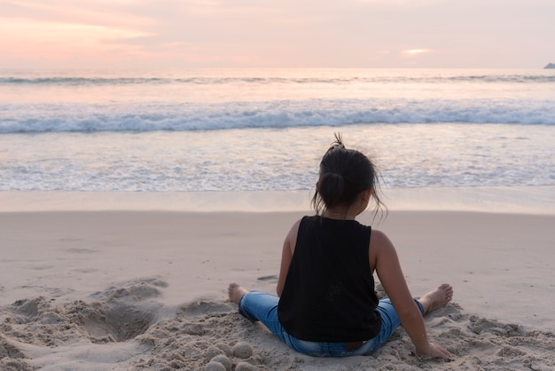 어린 소녀가 해변에서 모래 놀이