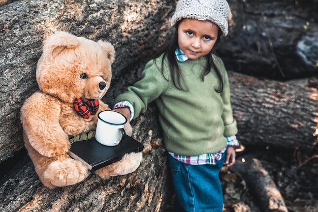 Маленькая девочка играет с медведем на бревнах.