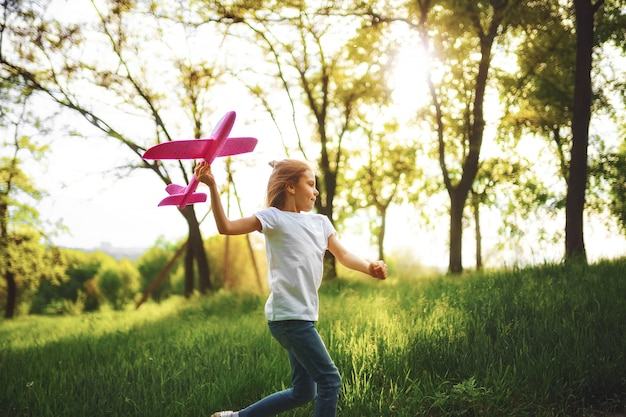 Little girl, play with a toy plane in the air in park.