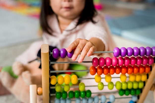 Маленькая девочка играет на счетах для практики счета
