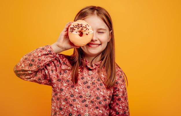 Маленькая девочка играет и держит пончик в очках рядом с глазами, изолированными на желтом фоне
