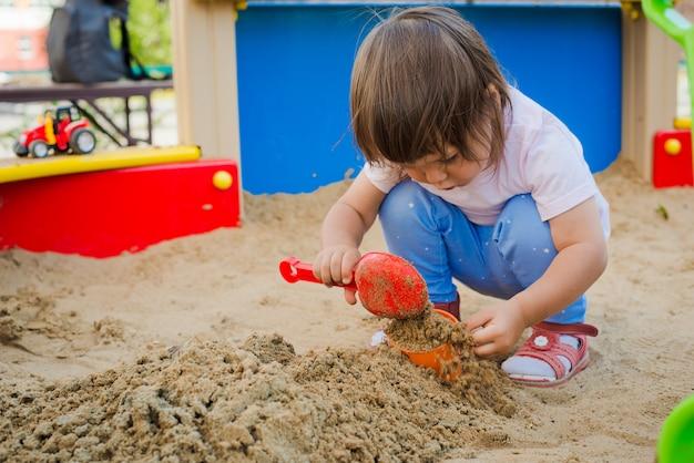 Little girl playing in asandbox