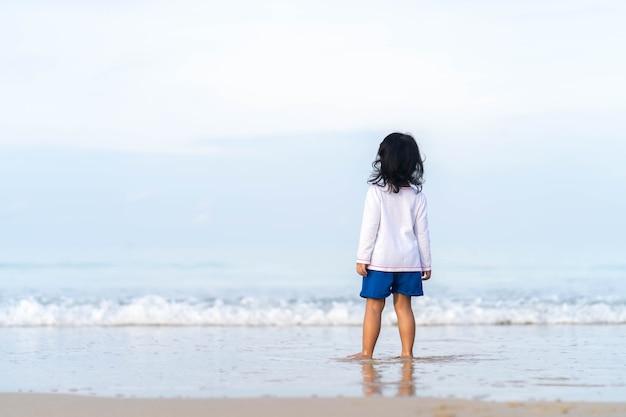 아름 다운 바다 해안에서 재생하는 어린 소녀.