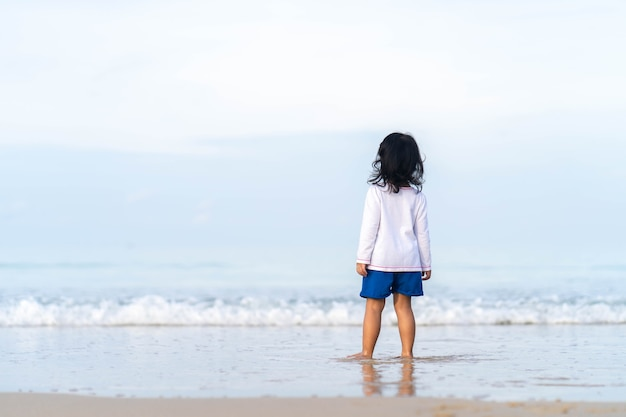 Little girl playing at beautiful sea shore.