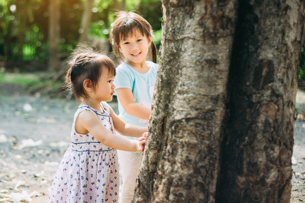 Little girl playing under the big tree