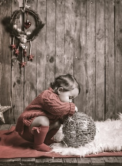Little girl playing in christmas decoration.
