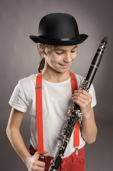 Little girl playing clarinet on gray