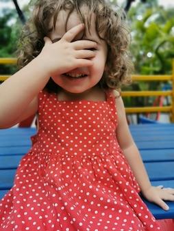 Маленькая девочка играет, закрывая лицо рукой