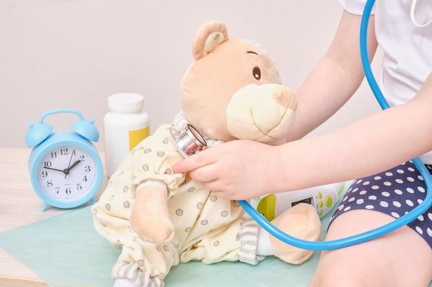 医者を演じて、聴診器の目覚まし時計と背景の丸薬でテディベアを聞いている少女