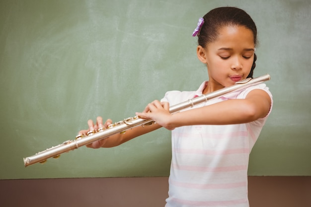 Little girl playing flute in classroom