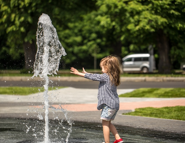 Little girl playing in the fountain